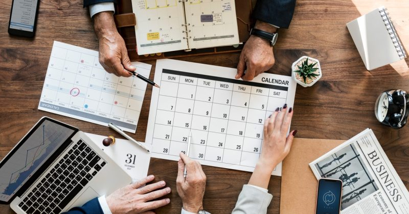 Business people planning around a calendar